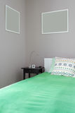 Green bed with bedside table Stock Photo