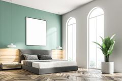 Green bedroom corner, frame poster. Green bedroom corner with a wooden floor, a king size bed and a frame vertical poster hanging above it. 3d rendering mock up Royalty Free Stock Image