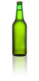 Green beer bottle. Green glass beer bottle reflecting on white background royalty free stock image
