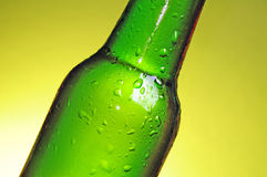 Green beer bottle. Green see through bottle of beer with tiny clear drops on its surface Royalty Free Stock Photos