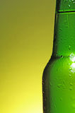 Green beer bottle. Green see through bottle of beer with tiny clear drops on its surface Royalty Free Stock Photo