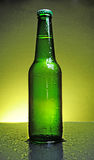 Green beer bottle. Green see through bottle of beer with tiny clear drops on its surface Royalty Free Stock Image