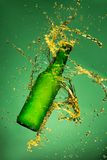 Green beer bottle with splashing liquid Royalty Free Stock Image