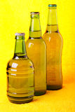 Green beer bottles against yellow Stock Image