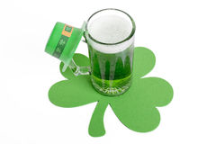 Green Beer. Cold, green beer in a glass mug, on a large shamrock stock image