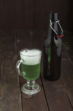 Green beer in glass with bottle on dark background Stock Image