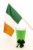 Green beer with Irish flag and shamrock. A glass of green beer with an Irish flag and a decorative shamrock royalty free stock photography
