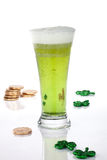 Green beer for St Patrick's Day. Glass of green beer for St Patrick's Day surrounded with gold coins and shamrock ornament Royalty Free Stock Photos