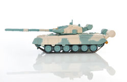 Green-and-beige toy tank on a white background. Royalty Free Stock Photo
