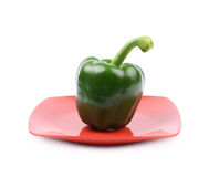 Green bell pepper on a plate. Green bell pepper on a red ceramic plate isolated over the white background Stock Photo