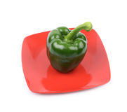 Green bell pepper on a plate. Green bell pepper on a red ceramic plate isolated over the white background Stock Photos