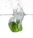 Green pepper in water. A green bell pepper splashing in water Stock Photos