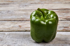 Green bell pepper on wood. Stock Photos