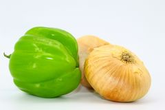 Green bell peppers and two onions placed on a light background stock photography