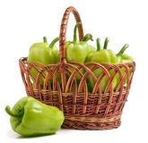 Green bell peppers in a wicker basket isolated on white background.  Stock Images