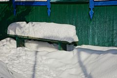 Green bench against a wall in white snow Royalty Free Stock Photography