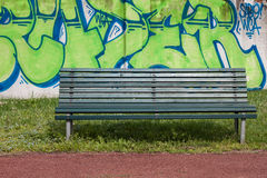 Green bench with graffiti on the background. Green bench in a city park with graffiti on the background Royalty Free Stock Photography