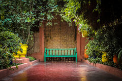Green bench in colouful garden surrounding. In the jardin de yves saint laurent in Royalty Free Stock Images