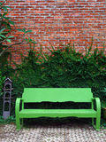 The green bench and Creeper Plant on red wall. The Green Creeper Plant on Wall Creates a Beautiful Background Royalty Free Stock Images
