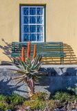 Green bench in front of a window Royalty Free Stock Photos