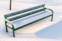 Green bench in a park covered with snow Royalty Free Stock Image