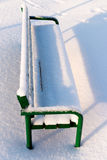 Green bench in a park covered with snow Stock Photography