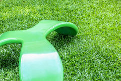 Green bench seat chair in three legs design on the green grass field Royalty Free Stock Image