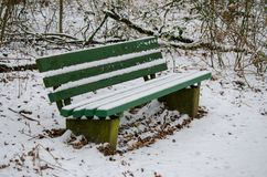 A green bench standing outside in a small forest Stock Photo