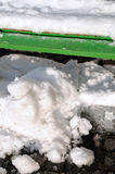 Green bench under snow. Melting snow on green bench at the end of winter Stock Photo