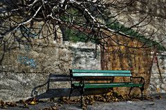 Green bench by the wall whit wall graffiti as background Stock Photos