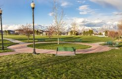Green Benches Around A Circular Pathway On A Park With Trees And Lamp Posts Royalty Free Stock Photo