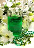 Green Beverage Closeup for St. Patrick`s Day, Beads. Festive green beads and gladiolas surrounding this mug filled with and Irish beverage.  Ideal for St Stock Photo