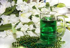 Green Beverage for St. Patrick`s Day, Beads. Festive green beads and gladiolas surrounding this mug filled with and Irish beverage.  Ideal for St. Patrick`s Day Royalty Free Stock Photos