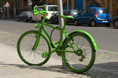 Green bicycle. Old green bicycle chained to a pole Stock Images