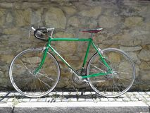 Green bicycle. In front of a stone wall stock photo