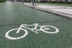 Green bicycle lane for biking, beside the walkway. In China royalty free stock photography