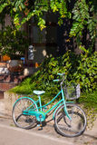 Green bicycle parked beside the house. Bike Stock Photos