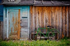 Green Bicycle by Wooden Building Royalty Free Stock Images