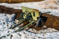 Green big gun in the snow with rusty barrel down Stock Photos