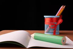 Green big pen and metal cup with crayons on desk on black background. Green big pen and metal cup with crayons on desk isolated on black background stock images