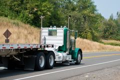Green big rig day cab semi truck with empty flat bed semi trailer driving to point of loads. Professional big rig day cab semi trucks with flat trailers are stock images