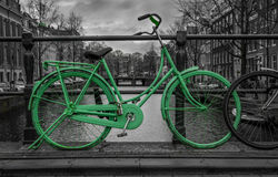Green bike Amsterdam. Green bike isolated on black and white over a canal in Amsterdam. Holland Royalty Free Stock Images