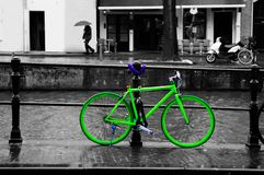 Green Bike on Black & White Rainy Background, Urban Dutch Scene royalty free stock image