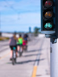 Green Bike traffic lights and riding cyclists Royalty Free Stock Image