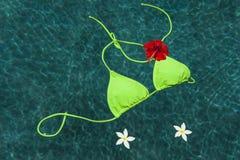 Green bikini floating with flowers Royalty Free Stock Photo