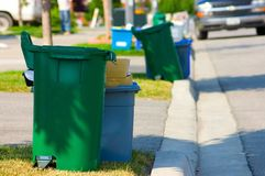 Green Bin. Green and blue recycling bins by the curb on a residential street Stock Photography