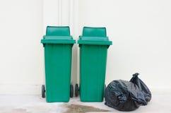 Green bin and Black garbage bags Stock Photo