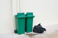 Green bin and Black garbage bags Royalty Free Stock Photo
