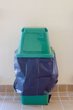 Green bin and Black garbage bags Royalty Free Stock Photography