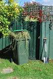 Green bin and spade in backyard Royalty Free Stock Image